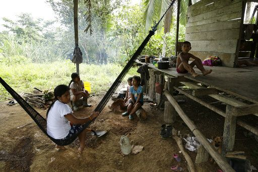 "Members of the Ngabe Bugle indigenous group sit at their home in the jungle community of El Terron, Panama, Friday, Jan. 17, 2020. A pregnant woman, five of her children and a neighbor where round up by about 10 lay preachers at the hamlet on Monday and tortured, beaten, burned and hacked with machetes to make them ""repent their sins"", authorities said."