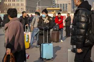 A traveler wears a facemask as she stands near the Beijing Railway Station in Beijing, Friday, Jan. 17, 2020. A second person has died from a new form of coronavirus in central China, health authorities said late Thursday. (AP Photo/Mark Schiefelbein)