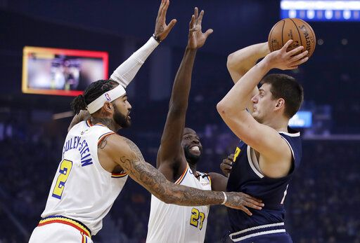 Denver Nuggets' Nikola Jokic, right, looks to pass the ball away from Golden State Warriors' Willie Cauley-Stein (2) and Draymond Green during the first half of an NBA basketball game Thursday, Jan. 16, 2020, in San Francisco.