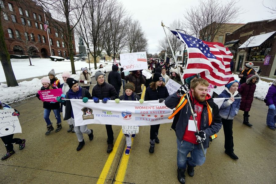 Participants in the Fox Valley Women's March make their way through downtown Geneva on Saturday, braving the low temperatures to promote messages of equality and the importance of political engagement.