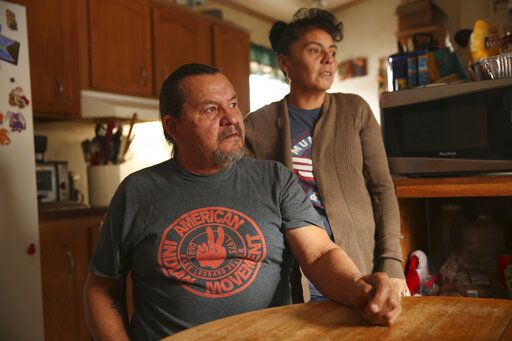 In this Dec. 11, 2019 photo, Henry Red Cloud, and Gloria Red Cloud, look out the window of their home on the Pine Ridge Indian Reservation in South Dakota. They fear what winter storms will do after flooding damaged their home last spring. They ran workshops on solar panel and wind turbine installation, but had to halt the classes when flooding damaged their tools and property.