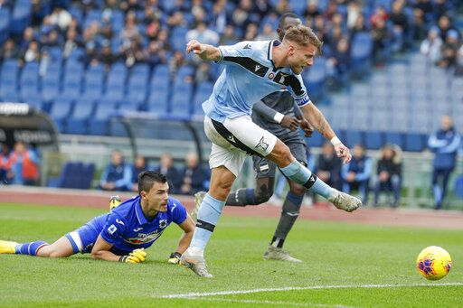 Lazio's Ciro Immobile, left, scores his side's third goal past Sampdoria's goalkeeper Emil Audero' during a Serie A soccer match between Lazio and Sampdoria, at Rome's Olympic Stadium, Saturday, Jan. 18, 2020.
