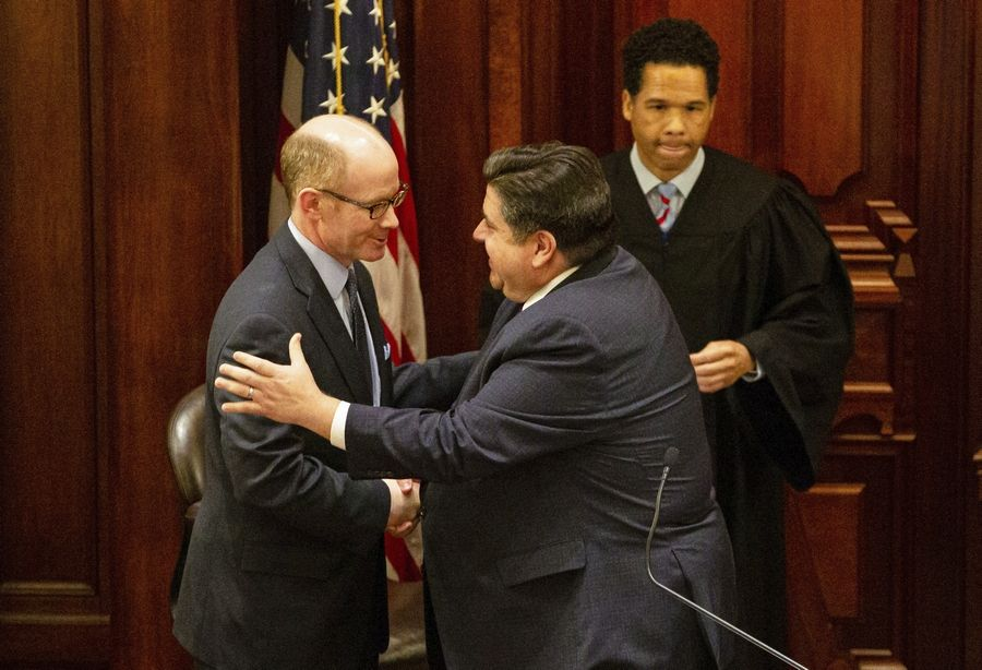 Gov. J.B. Pritzker greets Sen. Don Harmon before swearing him in Sunday as the next state Senate president.