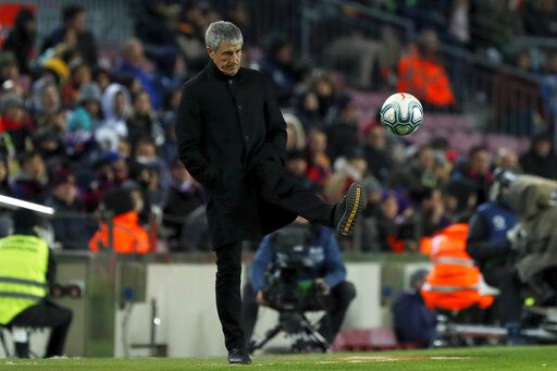 Barcelona's head coach Quique Setien kicks the ball back to the pitch during a Spanish La Liga soccer match between Barcelona and Granada at Camp Nou stadium in Barcelona, Spain, Sunday, Jan. 19, 2020.