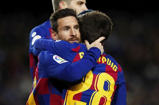 Barcelona's Lionel Messi, left, celebrates with Ricard Puig, right, after scoring the opening goal during a Spanish La Liga soccer match between Barcelona and Granada at Camp Nou stadium in Barcelona, Spain, Sunday, Jan. 19, 2020.