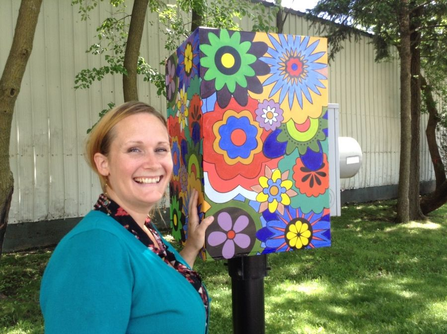 Jen Kehrer poses in 2014 with the utility box she painted as part of a village public art project. A new art project, using star-shaped models, is coming to town.
