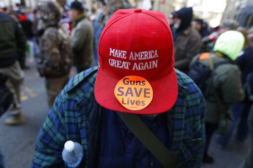 A man walks in the crowd during a pro-gun rally, Monday, Jan. 20, 2020, in Richmond, Va. Thousands of pro-gun supporters are expected at the rally to oppose gun control legislation like universal background checks that are being pushed by the newly elected Democratic legislature.