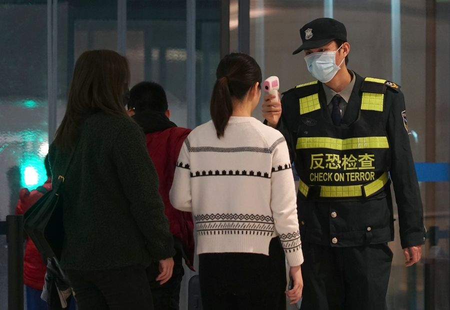 An airport staff member uses a temperature gun to check people leaving Wuhan Tianhe International Airport in Wuhan, China, Tuesday.