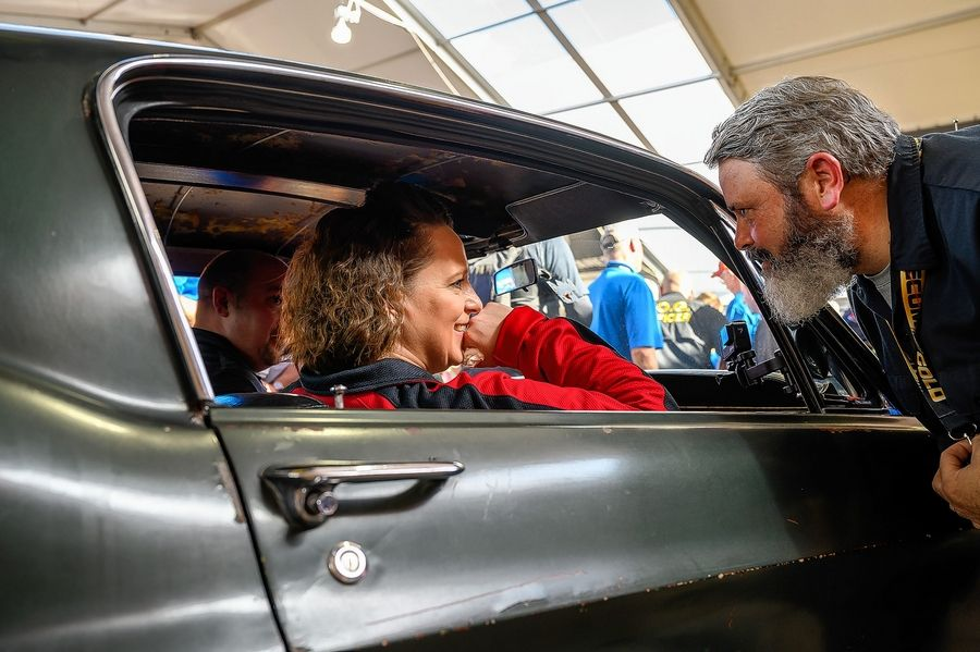 Kelly Cotton, whose parents purchased the car in 1974, talks with an eagar spectator. Below, people gather around to photogragh the Mustang, which in 2018 became the 21st vehicle named to the National Historic Vehicle Register by the Historic Vehicle Association.