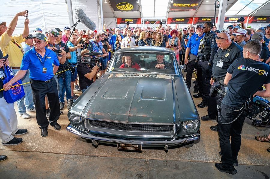 "Sean Kiernan and his sister, Kelly Cotton, ride in ""Bullitt"" as it is rolled up to the auction block recently in Kissimmee, Florida. Their parents bought the Mustang in 1974."
