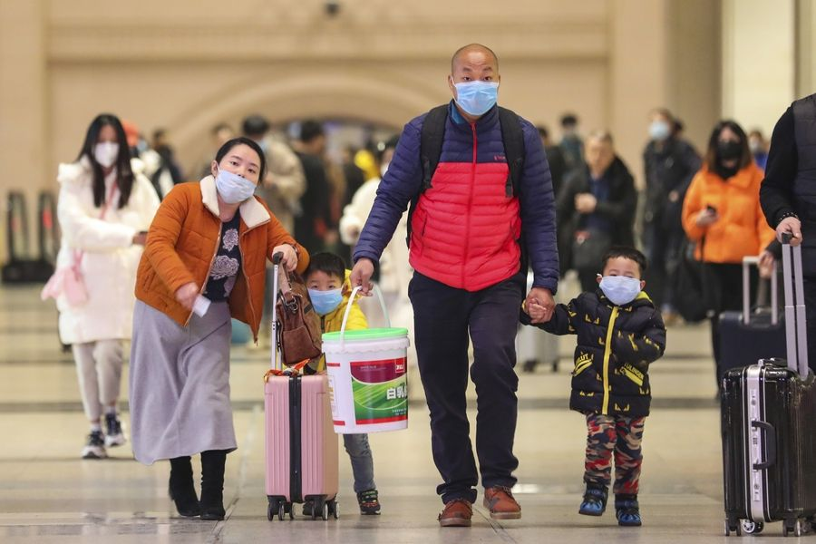Travelers wearing face masks Tuesday walk with their luggage at Hankou Railway Station in Wuhan in southern China's Hubei province. The U.S. on Tuesday reported its first case of a new and potentially deadly virus circulating in China, saying a Washington state resident who returned last week from the outbreak's epicenter was hospitalized near Seattle.
