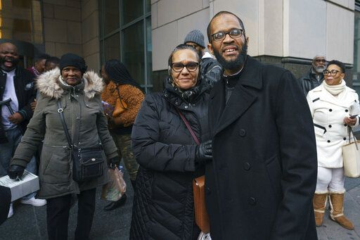 Kim Wilson, center, poses for a photo with her son Theophalis Wilson after he walks out of the Criminal Justice Center in Philadelphia on Tuesday, Jan. 21, 2020. Wilson, who served nearly three decades in prison for a Philadelphia triple murder, was freed Tuesday after a judge threw out his conviction. (Jessica Griffin/The Philadelphia Inquirer via AP)