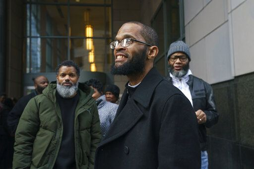 Theophalis Wilson, with friends and family behind him, walks out of the Criminal Justice Center in Philadelphia on Tuesday, Jan. 21, 2020, after being exonerated for a triple murder that took place when he was 17 years old, for which he served 21 years in prison. (Jessica Griffin/The Philadelphia Inquirer via AP)
