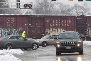 A stopped freight train on the Metra North Central line Thursday morning blocked traffic and caused delays for rail commuters as well.