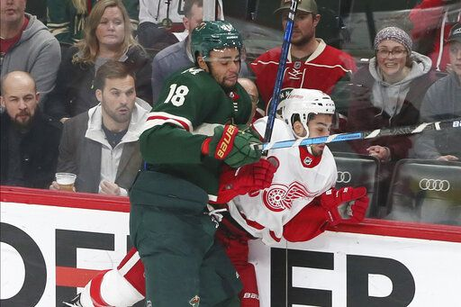 Minnesota Wild's Jordan Greenway, left, checks Detroit Red Wings' Robby Fabbri in the first period of an NHL hockey game Wednesday, Jan. 22, 2020, in St. Paul, Minn.
