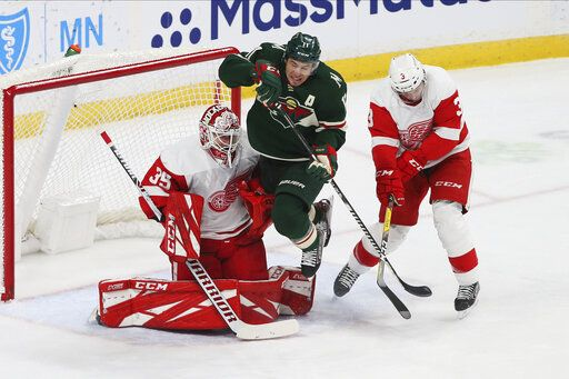 Minnesota Wild's Zach Parise, center, jumps to clear the way for a shot as Detroit Red Wings' goalie Jimmy Howard, left, defends in the first period of an NHL hockey game Wednesday, Jan. 22, 2020, in St. Paul, Minn.