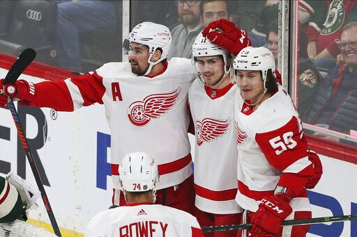 Detroit Red Wings' Filip Zadina, center, of Czech Republic is congratulated by teammates on his first of two goals off Minnesota Wild's Devan Dubnyk in the first period of an NHL hockey game Wednesday, Jan. 22, 2020, in St. Paul, Minn.