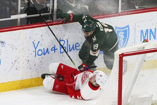 Minnesota Wild's Luke Kunin, right, sends Detroit Red Wings' Carson Soucy to the ice in the first period of an NHL hockey game Wednesday, Jan. 22, 2020, in St. Paul, Minn.