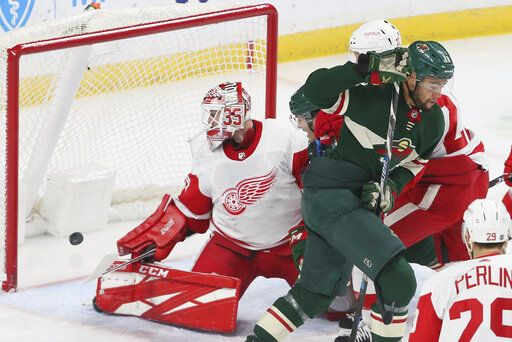 Minnesota Wild's Jordan Greenway, right, skates away after scoring against Detroit Red Wings' goalie Jimmy Howard, left, in the first period of an NHL hockey game Wednesday, Jan. 22, 2020, in St. Paul, Minn.