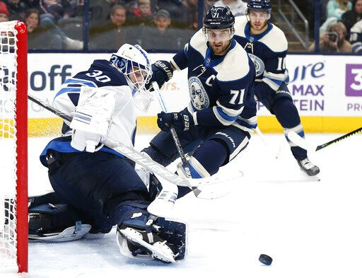 Winnipeg Jets' Laurent Brossoit, left, makes a save against Columbus Blue Jackets' Nick Foligno during the second period of an NHL hockey game Wednesday, Jan. 22, 2020, in Columbus, Ohio.
