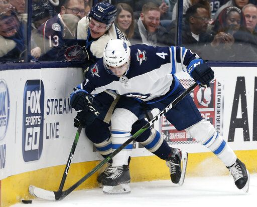 Winnipeg Jets' Neal Pionk, right, checks Columbus Blue Jackets' Eric Robinson during the second period of an NHL hockey game Wednesday, Jan. 22, 2020, in Columbus, Ohio.