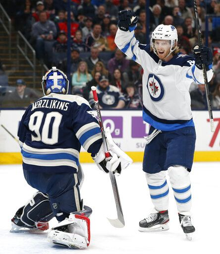Winnipeg Jets' Kyle Connor, right, celebrates his goal against Columbus Blue Jackets' Elvis Merzlikins, of Latvia, during the first period of an NHL hockey game Wednesday, Jan. 22, 2020, in Columbus, Ohio.