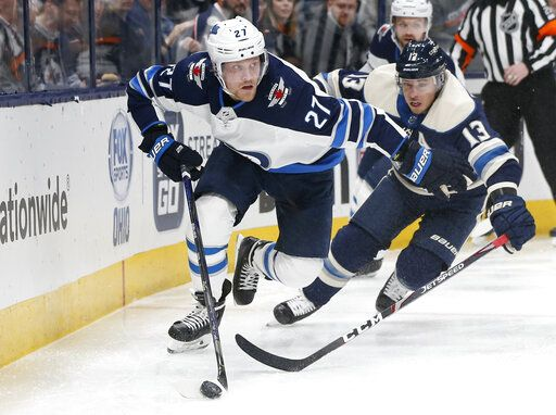 Winnipeg Jets' Nikolaj Ehlers, left, of Denmark, tries to clear the puck as Columbus Blue Jackets' Cam Atkinson chases him behind the net during the second period of an NHL hockey game Wednesday, Jan. 22, 2020, in Columbus, Ohio.