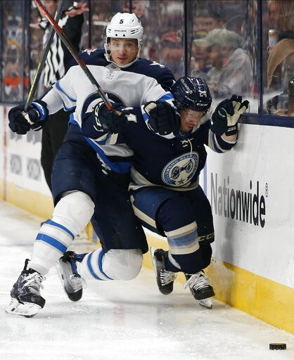 Winnipeg Jets' Luca Sbisa, left, of Italy, checks Columbus Blue Jackets' Nathan Gerbe during the second period of an NHL hockey game Wednesday, Jan. 22, 2020, in Columbus, Ohio.