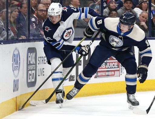Winnipeg Jets' Blake Wheeler, left, and Columbus Blue Jackets' Zach Werenski fight for a loose puck during the first period of an NHL hockey game Wednesday, Jan. 22, 2020, in Columbus, Ohio.