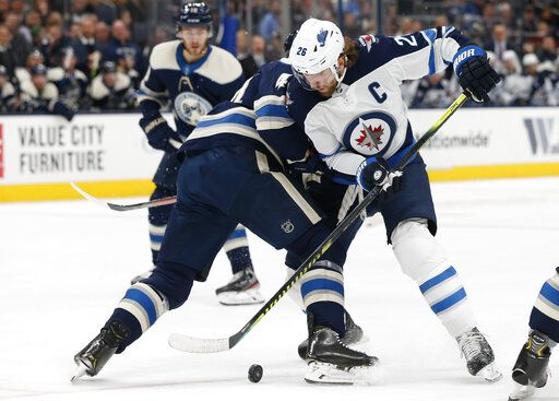Winnipeg Jets' Blake Wheeler, right, tries to carry the puck past Columbus Blue Jackets' Vladislav Gavrikov, of Russia, during the first period of an NHL hockey game Wednesday, Jan. 22, 2020, in Columbus, Ohio.