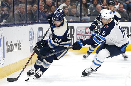 Columbus Blue Jackets' Nathan Gerbe, left, looks for an open pass as Winnipeg Jets' Luca Sbisa, of Italy, defends during the second period of an NHL hockey game Wednesday, Jan. 22, 2020, in Columbus, Ohio.