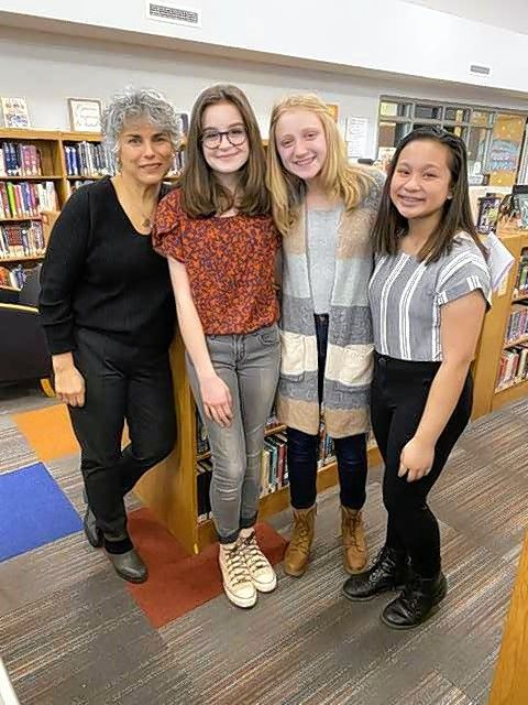 From left, Fern Schumer Chapman meets with Viking Middle School students Clara Hooker, Abigail Harris and Erika Relayson, who interviewed the author.