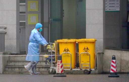 FILE - In this Wednesday, Jan. 22, 2020, file photo, a staff member moves bio-waste containers past the entrance of the Wuhan Medical Treatment Center in Wuhan, China, where some people infected with a new virus are being treated. The new virus comes from a large family of coronaviruses, some causing nothing worse than a cold. Others named SARS and MERS have killed hundreds in separate outbreaks.