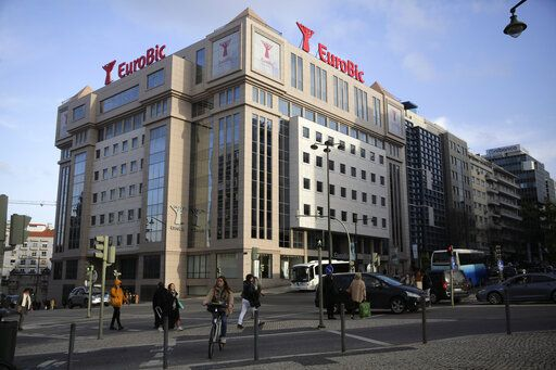 People walk past the building of Lisbon-based bank EuroBic in Lisbon, Thursday, Jan. 23, 2020. The head of private banking at EuroBic, who was named in a major Angolan money-laundering and corruption scandal, has died in an apparent suicide at home in Lisbon, police said Thursday.