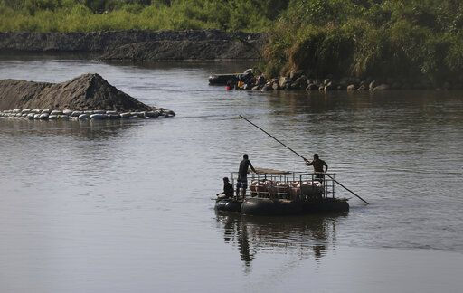 Men transport pigs across the Suchiate River, from Mexico to Guatemala, as they move away from Ciudad Hidalgo, Mexico, Friday, Jan. 24, 2020, a location popular for migrants to cross from Guatemala to Mexico.
