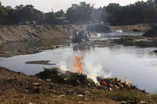 Trash left behind by Central American migrants is burned, set fire by locals who operate the small ferries on the Suchiate River near Ciudad Hidalgo, Mexico, Friday, Jan. 24, 2020, a location popular for migrants to cross from Guatemala to Mexico.