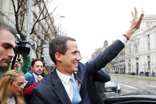 The leader of Venezuela's political opposition Juan Guaido waves during a visit to Madrid, Spain, Saturday, Jan. 25, 2020. Juan Guaido, the man who one year ago launched a bid to oust Venezuelan President Nicolas Maduro, arrived Saturday in Spain, where a thriving community of Venezuelans and a storm among Spanish political parties awaited him.