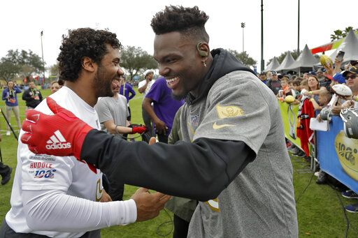 NFC linebacker Shaquil Barrett, of the Tampa Bay Buccaneers,, right, shakes hands with quarterback Russell Wilson, of the Seattle Seahawks, after a practice for the NFL Pro Bowl football game Thursday, Jan. 23, 2020, in Kissimmee, Fla.