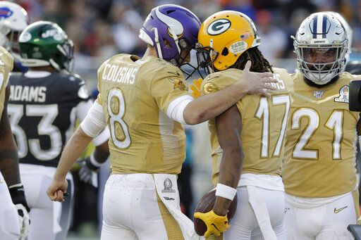 NFC quarterback Kirk Cousins, of the Minnesota Vikings, congratulates NFC wide receiver Davante Adams, of the Green Bay Packers, after Adams scored a touchdown, during the second half of the NFL Pro Bowl football game against the AFC, Sunday, Jan. 26, 2020, in Orlando, Fla.