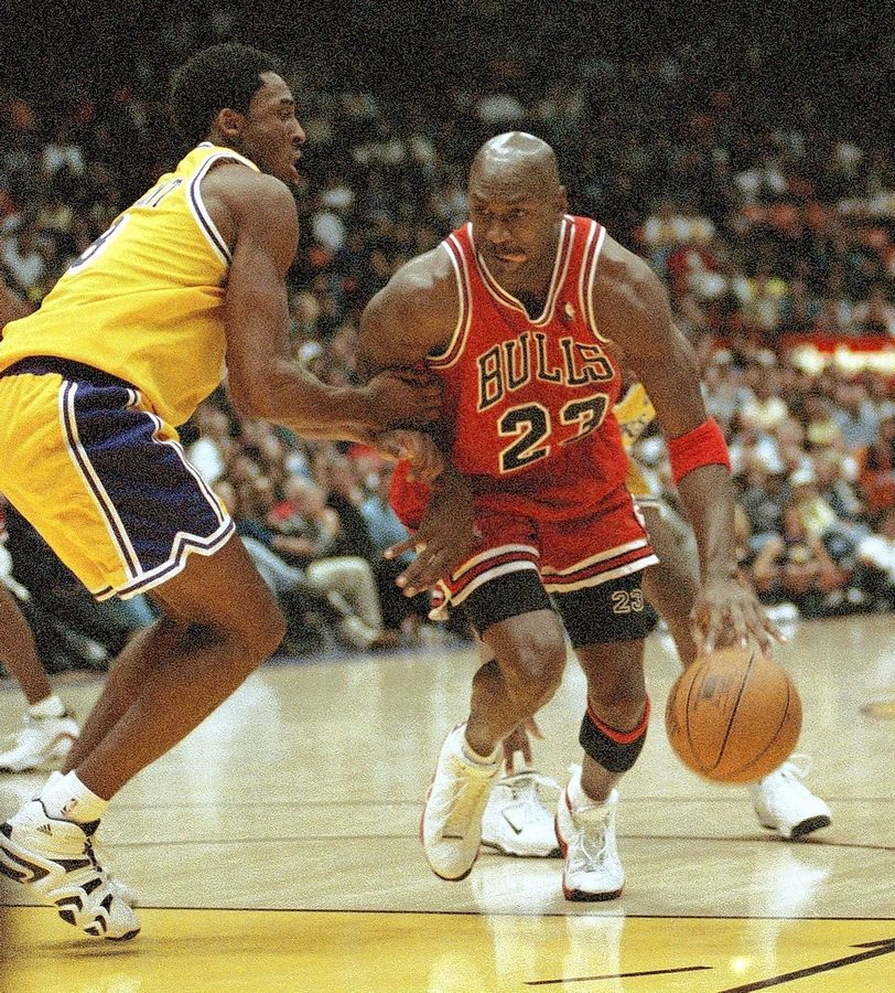 Michael Jordan is held up by Kobe Bryant during a game the Lakers won handily Feb. 1, 1998 in Inglewood, Calif.