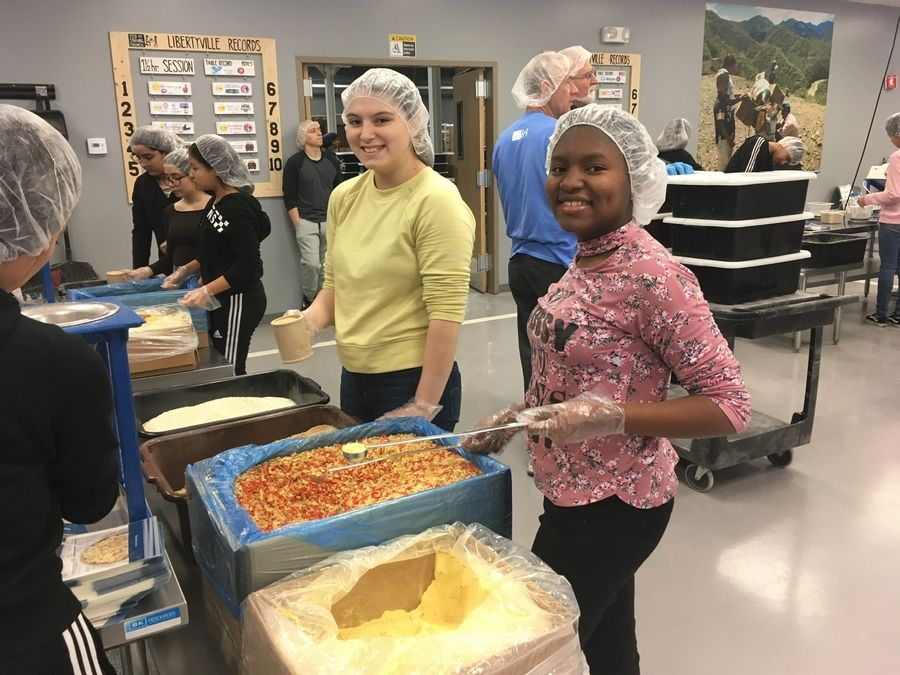 Two NJHS members from Zion Central Middle School work together to package meals (Marsha DeBennette)