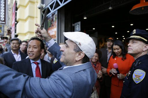 File - In this Nov. 20, 2018, file photo, owner Nick Bovis prepares to cut a ribbon during the opening of Lefty O'Doul's Baseball Ballpark Buffet & Café at Fisherman's Wharf in San Francisco. Looking on are state assemblyman David Chiu, second from left, San Francisco Mayor London Breed, second from right and city public works director Mohammed Nuru, third from right. A top San Francisco official in charge of cleaning up the city's notoriously filthy streets and a champion of adding more portable toilets has been arrested, jail records show. San Francisco Public Works Director Mohammed Nuru was taken into custody Monday, Jan. 27, 2020, along with Nick Bovis, the owner of Lefty O' Doul's, a longtime sports bar popular with tourists. Records say only that the men were arrested for felony safekeeping, which typically indicates federal charges.