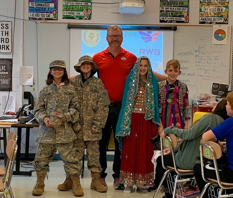"Franklin Middle School teacher Jack Erwin, an Army veteran, stands with his students during a history class. The lesson focuses on a book, ""The Breadwinner,"" which ties in well with his presentation about his deployment to Afghanistan, he says."
