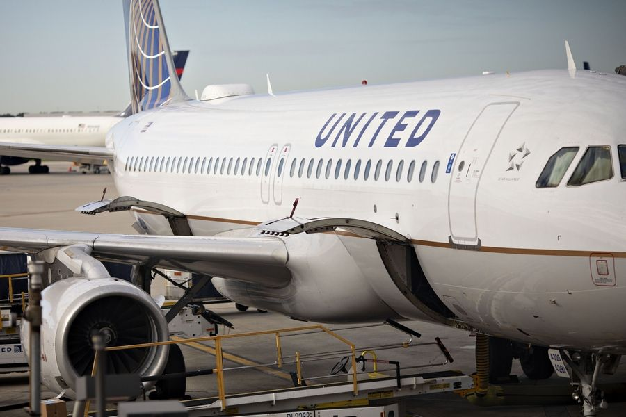 A United Airlines aircraft sits at a gate at O'Hare International Airport. The Chicago-based airline is buying a flight-training school to help increase the supply of future pilots.