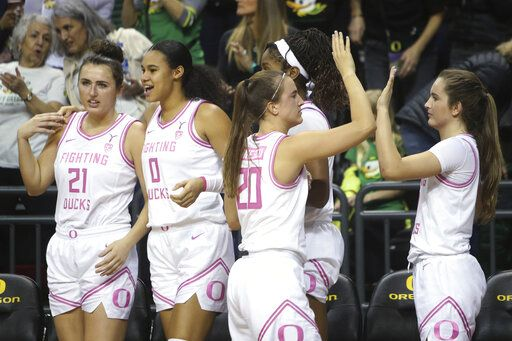 Oregon's Erin Boley, Satou Sabally, Sabrina Ionescu, Ruthy Hebard and Taylor Chavez, from left, celebrate in the closing seconds of the team's NCAA college basketball game in against Arizona in Eugene, Ore., Friday, Feb. 7, 2020.