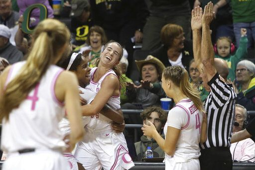 Oregon's Ruthy Hebard, center left, hugs Sabrina Ionescu, as Jaz Shelley, right, watches after Ionescu made a 3-point shot at the buzzer to end the third quarter of the team's NCAA college basketball game against Arizona in Eugene, Ore., Friday, Feb. 7, 2020.