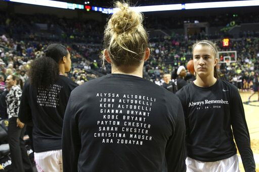Oregon's Satou Sabally, left, Holly Winterburn and Sabrina Ionescu, right, wear T-shirts honoring the people lost in the helicopter crash along with Kobe Bryant, before the team's NCAA college basketball game against Arizona in Eugene, Ore., Friday, Feb. 7, 2020.