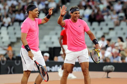 Trevor Noah and Rafael Nadal high five after winning a point against Roger Federer and Bill Gate in the exhibition match held at the Cape Town Stadium in Cape Town, South Africa, Friday Feb. 7, 2020.