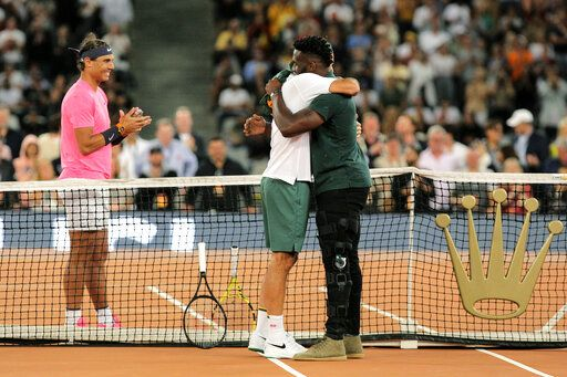 Springbok Captain Siya Kolisi, right, greets Roger Federer while Rafael Nadal looks on ahead of their exhibition tennis match held at the Cape Town Stadium in Cape Town, South Africa, Friday Feb. 7, 2020.