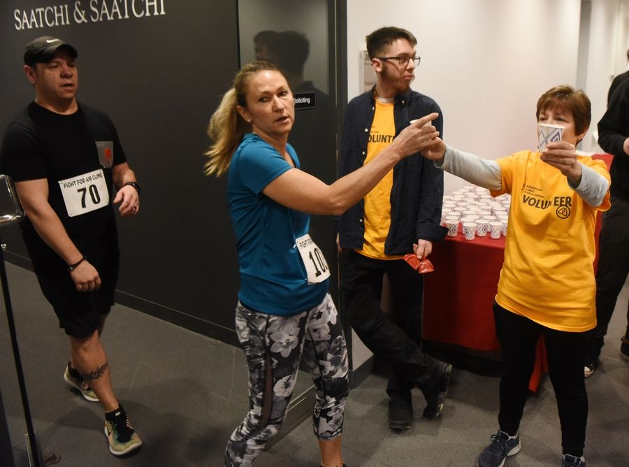 Pete Villicana of Aurora, left, and Janis Dennis of Tinley Park, second from left, are greeted at the top of 31 flights of stairs during the American Lung Association Fight for Air Climb at the Oakbrook Terrace Tower Saturday.